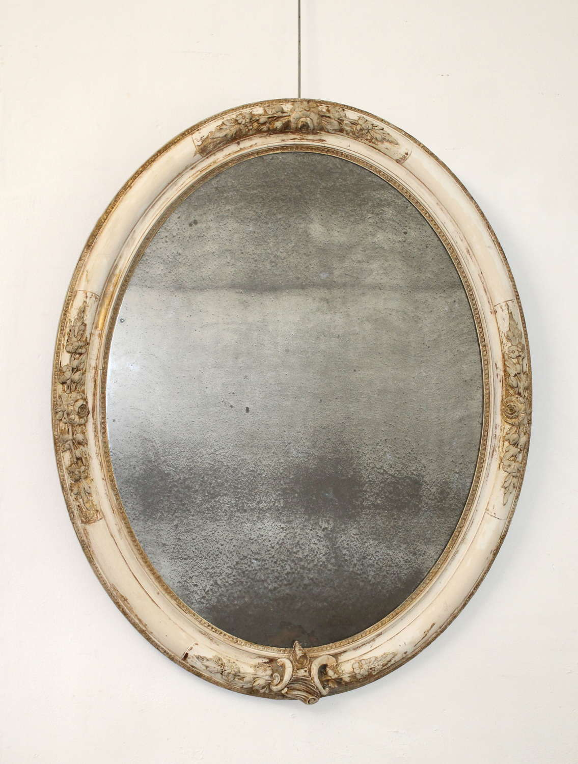 Large antique oval mirror with foxed mercury glass